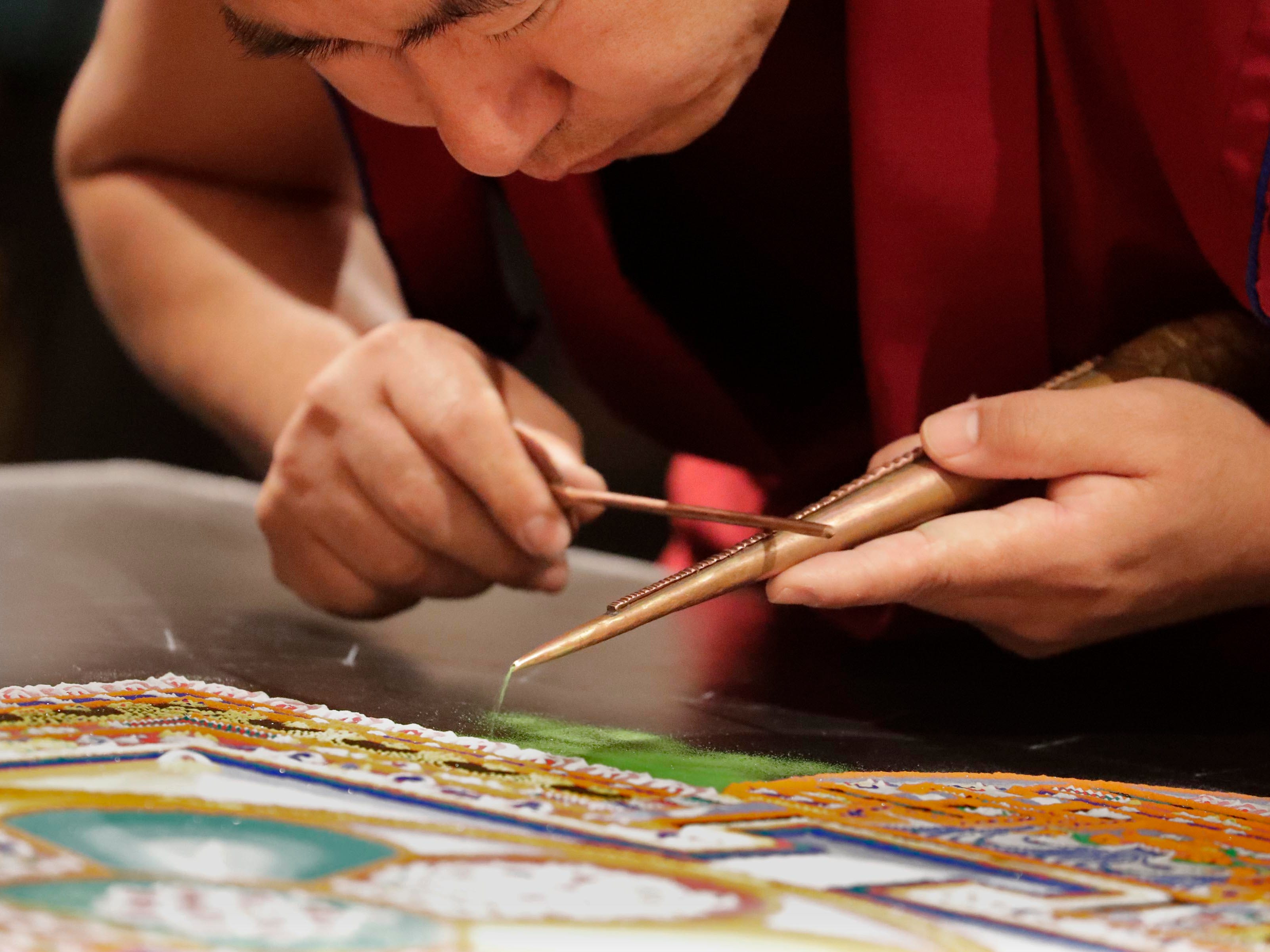 Choegyal Sangpo, a Buddhist monk,  creates vibrations on the funnel to create a flow of sand to create the mandala. Buddhist monks from the Drepung Loseling Monastery, mix bowls of colorful sand and use funnels to apply the sand and create a  sand mandala in the center of Milwaukee's City Hall, Thursday, April 11, 2019.
