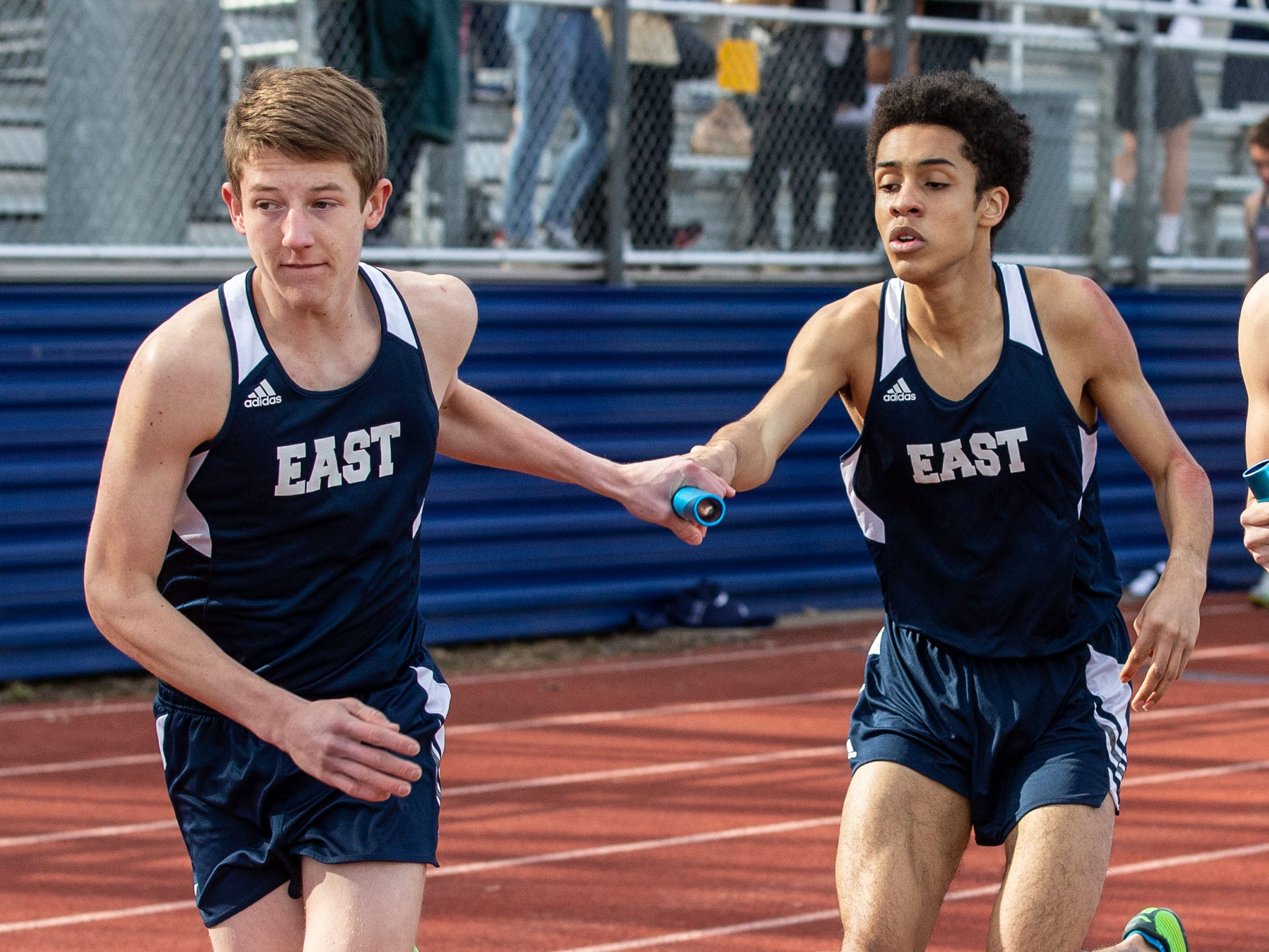 Brookfield East's Ian Szablewski (left) takes the baton from Langston Ford in the 4x800 meter relay during the Mike Gain 50th Annual Spartan Invitational at Brookfield East on Tuesday, April 9, 2019.