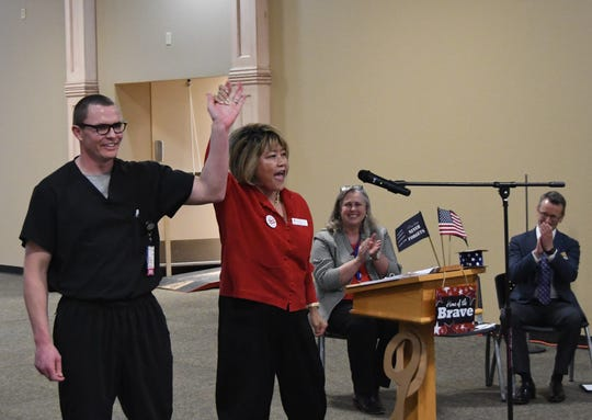Brian Barnett (far left) has his hand raised by STGi owner and CEO Michelle Lee during Wednesday's ceremony to celebrate the expansion of the Mountain Home Community-Based Outpatient Clinic. Applauding in the background are Dr. Tina McClain, chief of staff for the Central Arkansas Veterans Healthcare System, and Jeff Bell, STGi's COO.