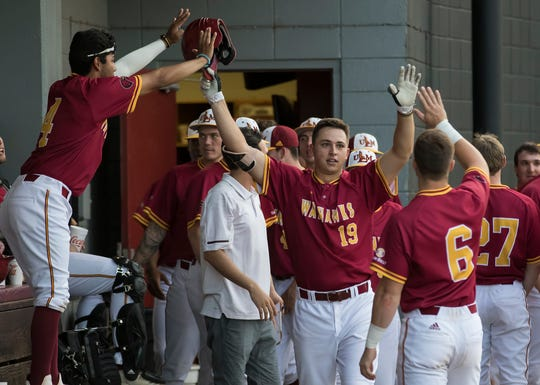 University of Louisiana at Monroe's Chad Bell (19) high fives his teammates in the dugout after his 3 run homerun in the bottom of second giving ULM a 3-2 lead over Northwestern State University during the game at Warhawk Field in Monroe, La. on April 10. ULM would go on to win the game 8-4.