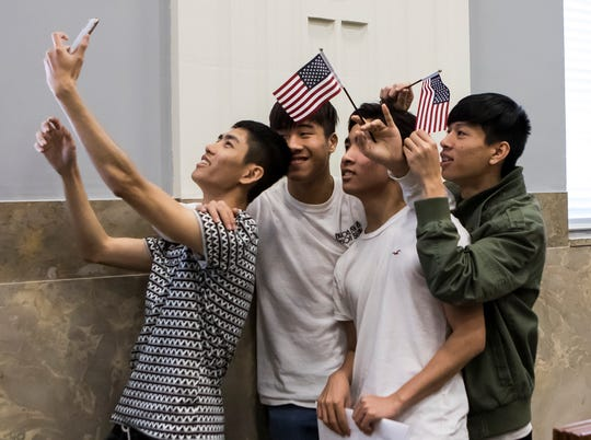 Linh Chung takes a selfie with Han Lu, C-Jay Vo and Mai Hieu after Vo and his brother Kelvin Vo (not pictured) became United States citizens during a ceremony at the federal courthouse in downtown Monroe, La. on April 10.