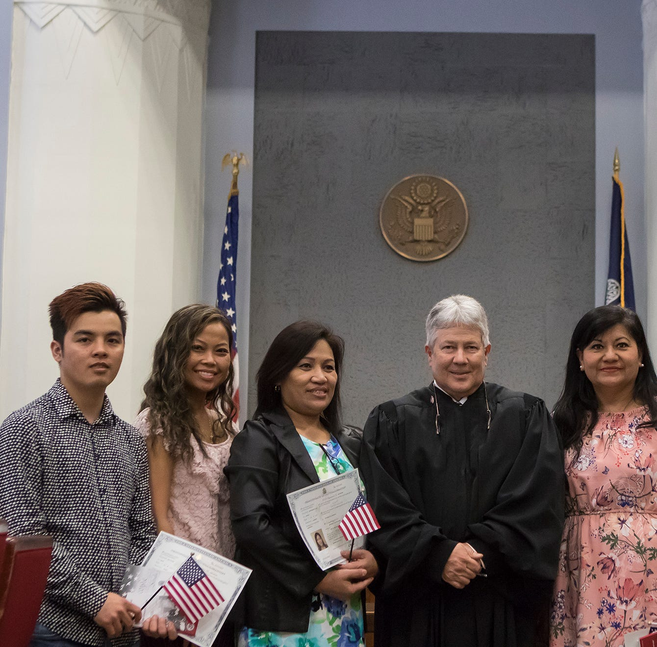 United States District Judge for the Western District of Louisiana Terry Doughty, center, stands with the six new United States citizens after a naturalization ceremony in the federal courthouse in downtown Monroe, La. on April 10.