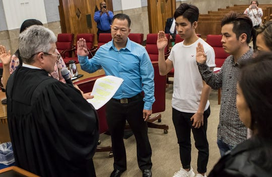 United States District Judge for the Western District of Louisiana Terry Doughty, center, leads six new United States citizens in the Oath of Allegiance during a naturalization ceremony in the federal courthouse in downtown Monroe, La. on April 10.