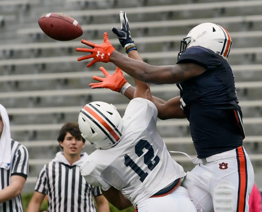 Auburn's Seth Williams (18) goes up for a catch over Devan Barrett (12) during a scrimmage in Auburn, Ala.