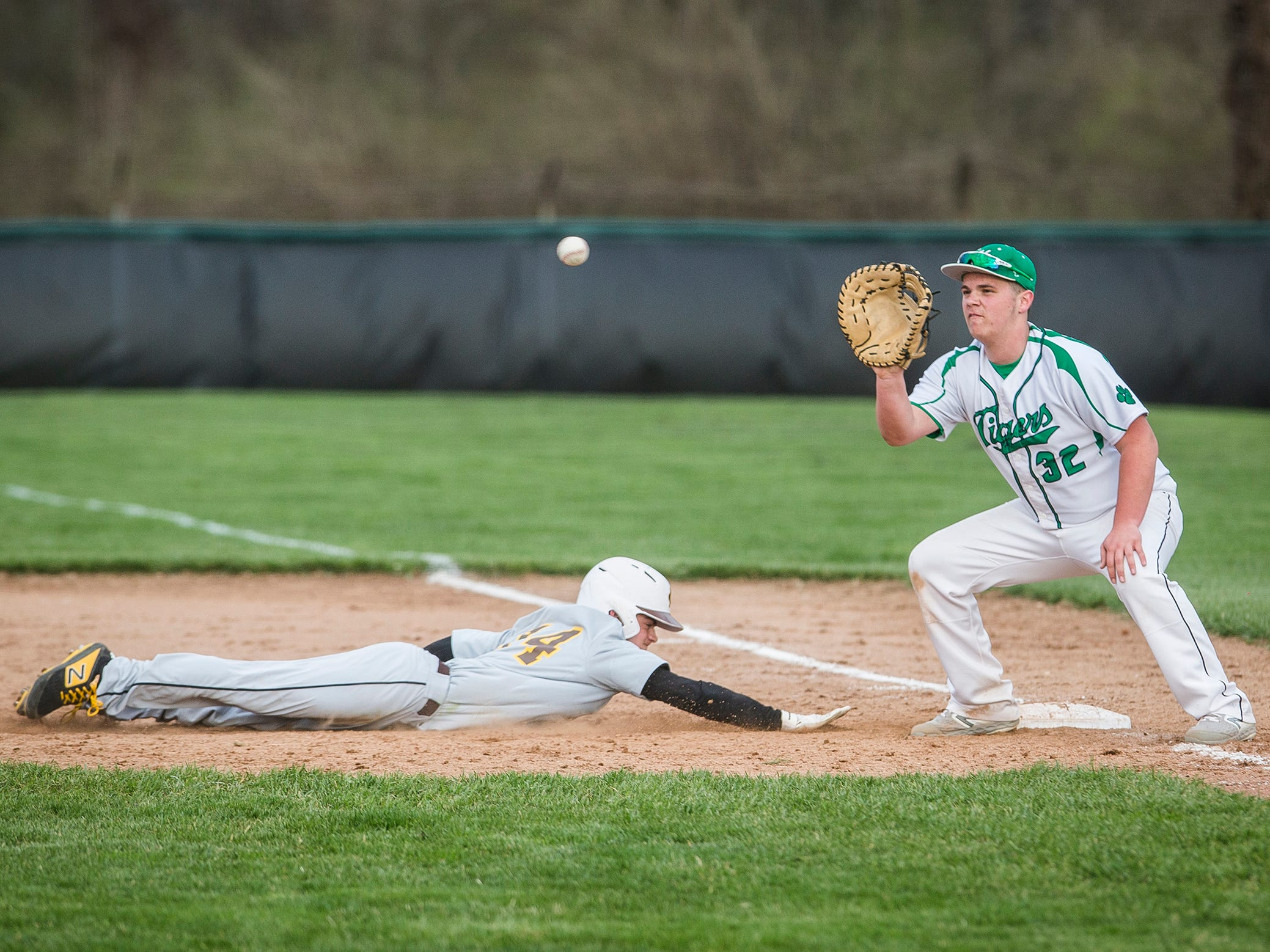 Yorktown's Billy McNamara attempts an out at first against Monroe Central during their game at Yorktown High School Wednesday, April 10, 2019.
