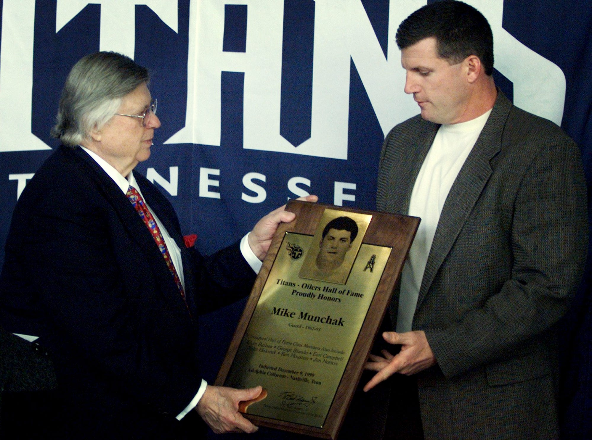 "Tennessee Titans owner K. S. ""Bud"" Adams, left, presents Mike Munchak with a plaque commemorating his induction in to the Titans/Oilers Hall of Fame for his play as guard for the Houston Oilers from 1982-1993 during a luncheon Dec. 9, 1999."