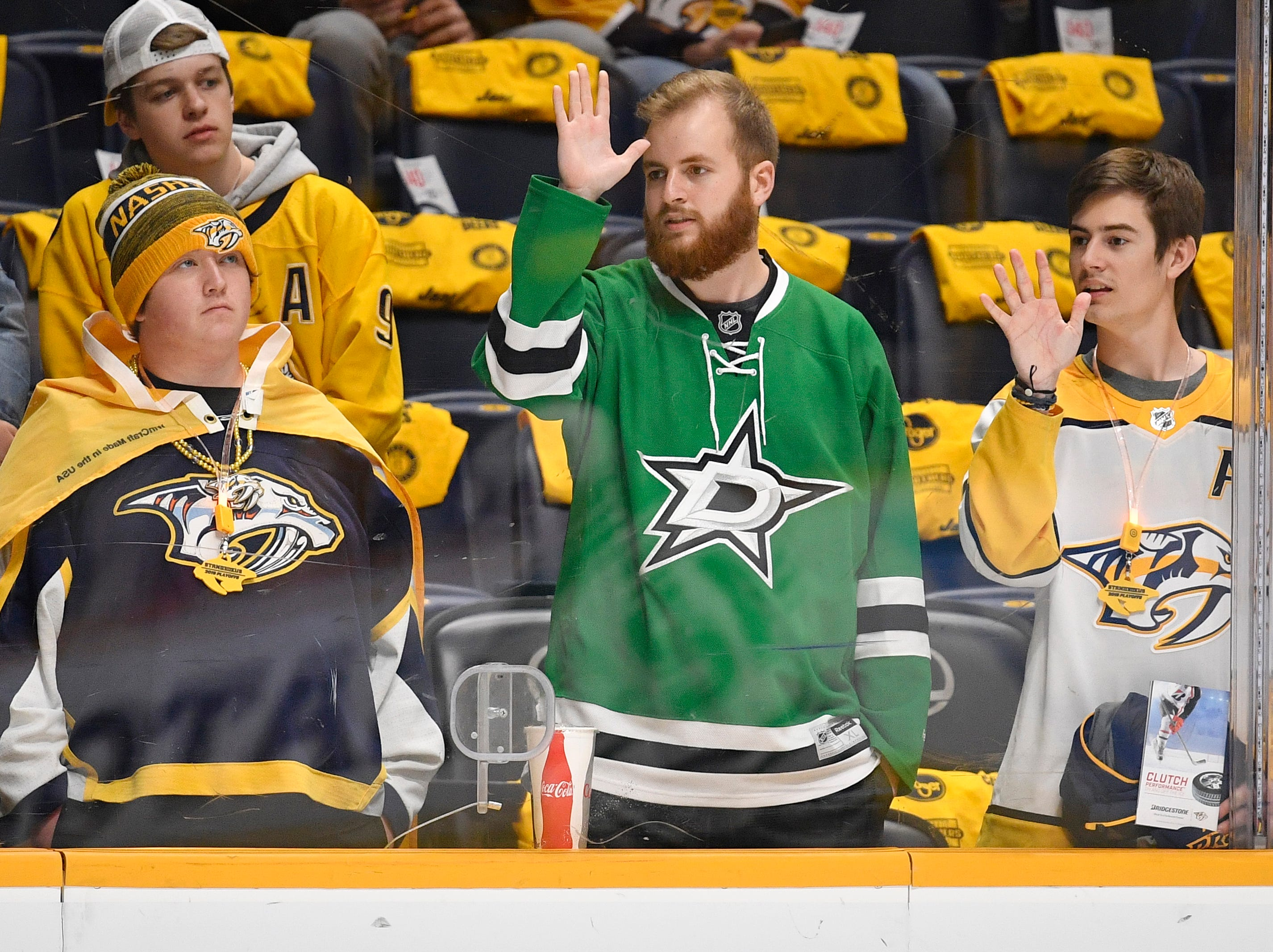 A Dallas fan is surrounded by Nashville fans watching warmups before the divisional semifinal game at Bridgestone Arena in Nashville, Tenn., Wednesday, April 10, 2019.