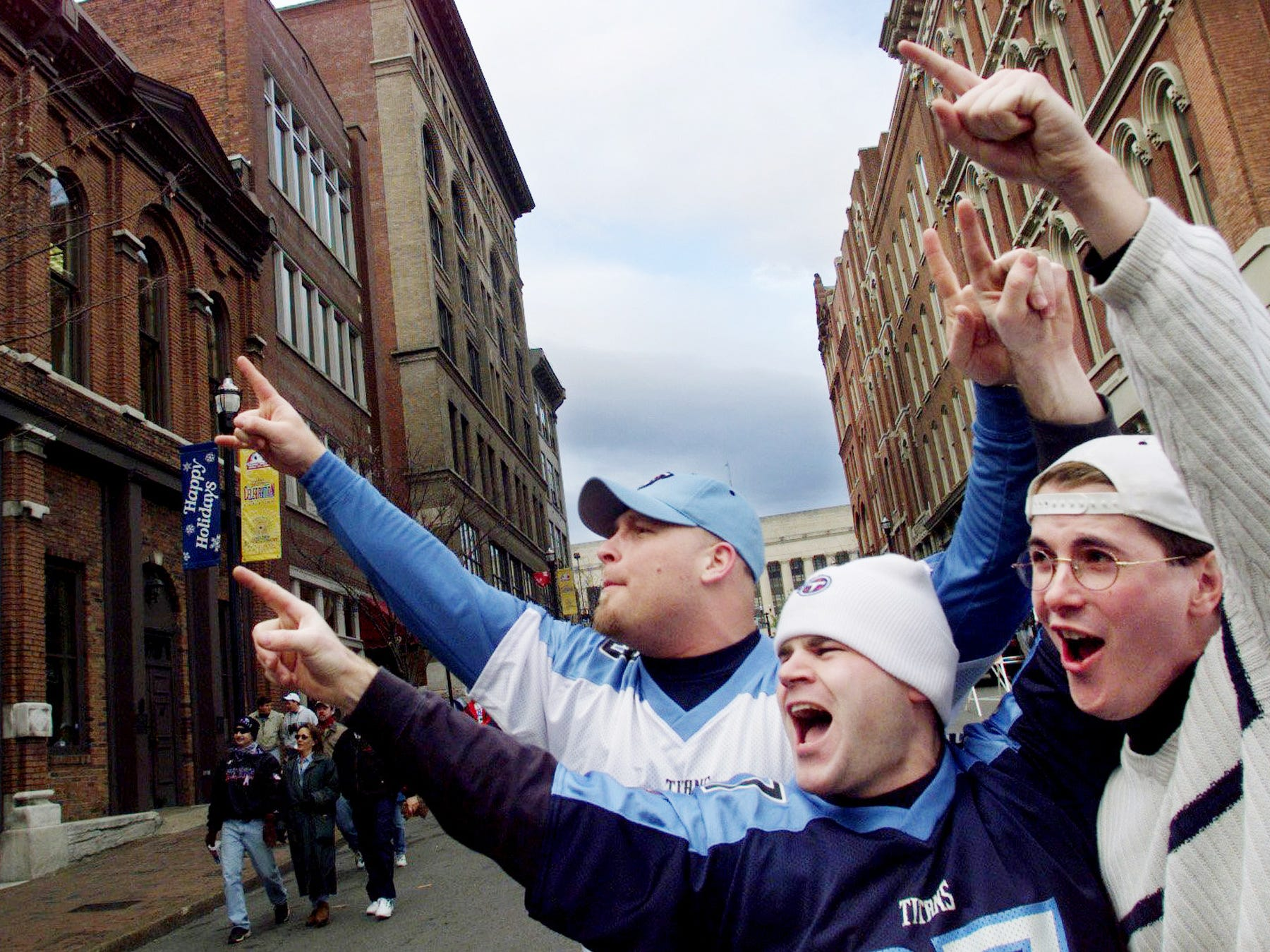 Barry Vargas, left, of Washington, D.C., Mike Steplowski and Jason Fitz, both of Antioch, go wild on Second Avenue with fellow fans in a second-story window as they walked back from the Adelphia Coliseum after the Tennessee Titans comeback playoff win over the Buffalo Bills Jan. 8, 2000.