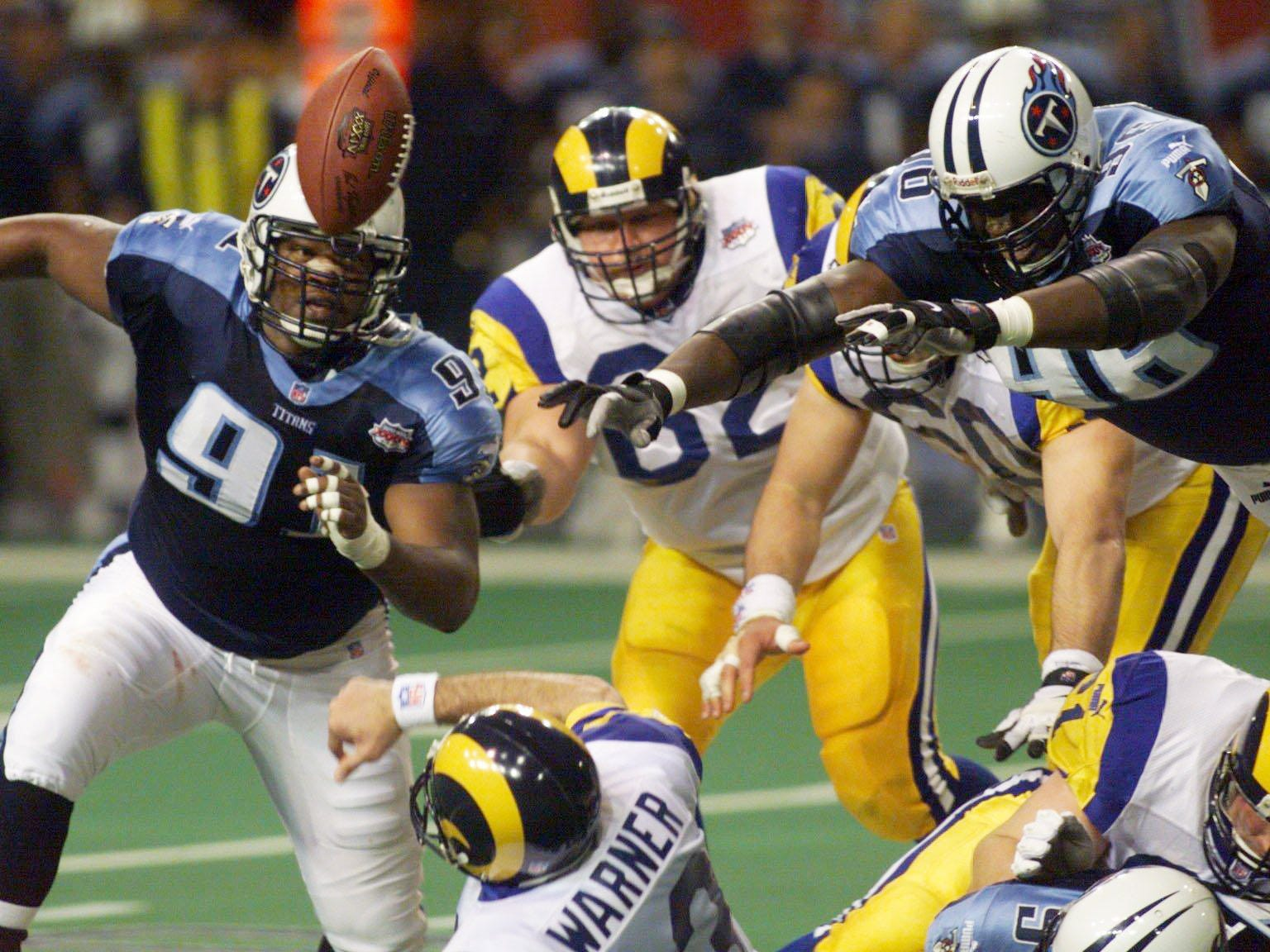 Tennessee Titans defenders Josh Evans (91), and Mike Jones (96), chase the ball as it popped loose from St. Louis Rams quarterback Kurt Warner (13), during second quarter action during Super Bowl XXXIV Jan. 30, 2000. Warner was ruled down on the play.