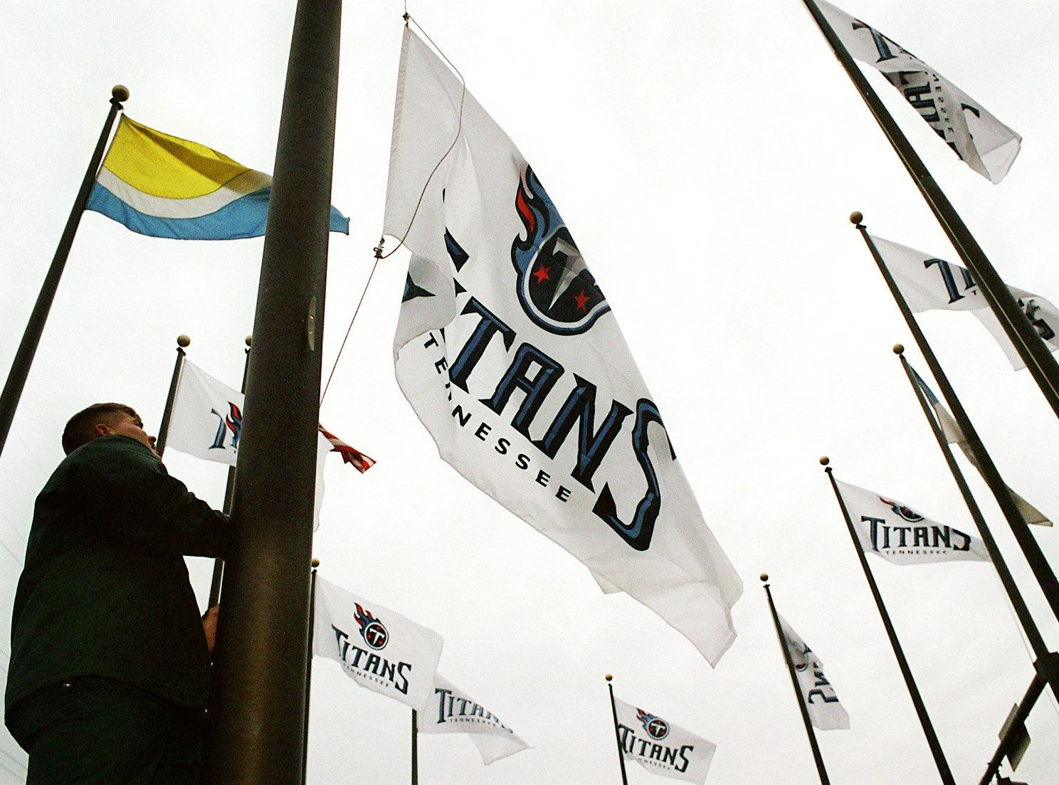 Metro Parks employee William Bryant hangs 10 Titans flags at Riverfront Park, replacing all but the U.S. Flag and the Riverfront Park flags Jan. 28, 2000 as the Titans get ready to face the St. Louis Rams in Super Bowl XXXIV.