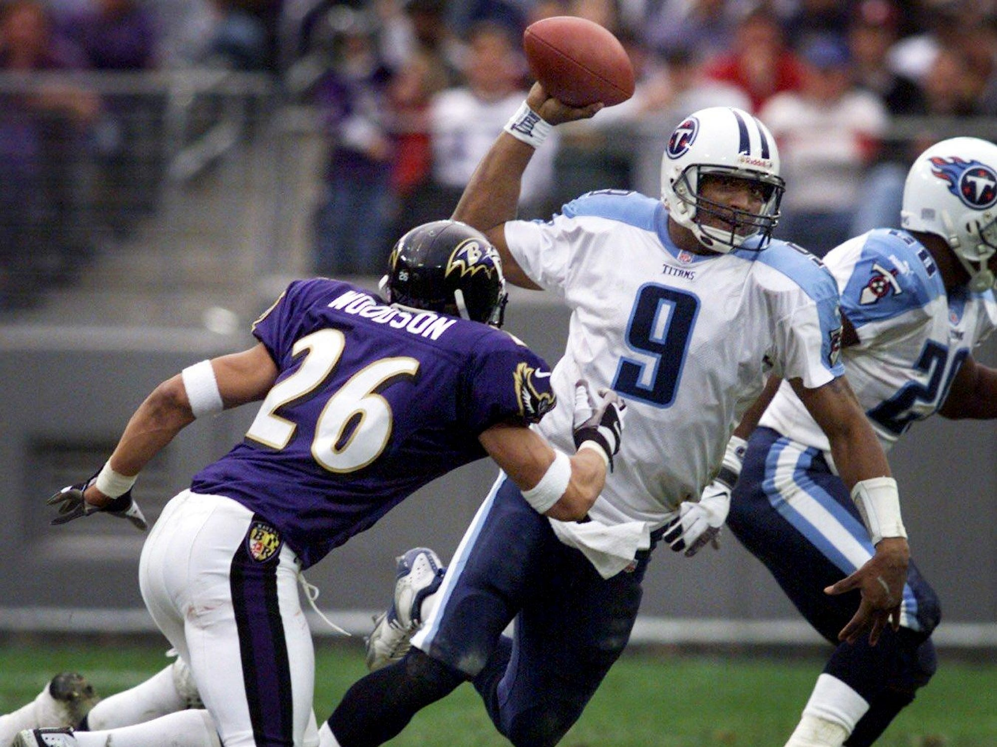 Tennessee Titans quarterback Steve McNair (9) scrambles to make a pass as Baltimore Ravens defensive back Rod Woodson (26) closes in for a sack, but the play ended as an incomplete pass. The Titans got beaten badly 41-14 on the road Dec. 5, 1999.