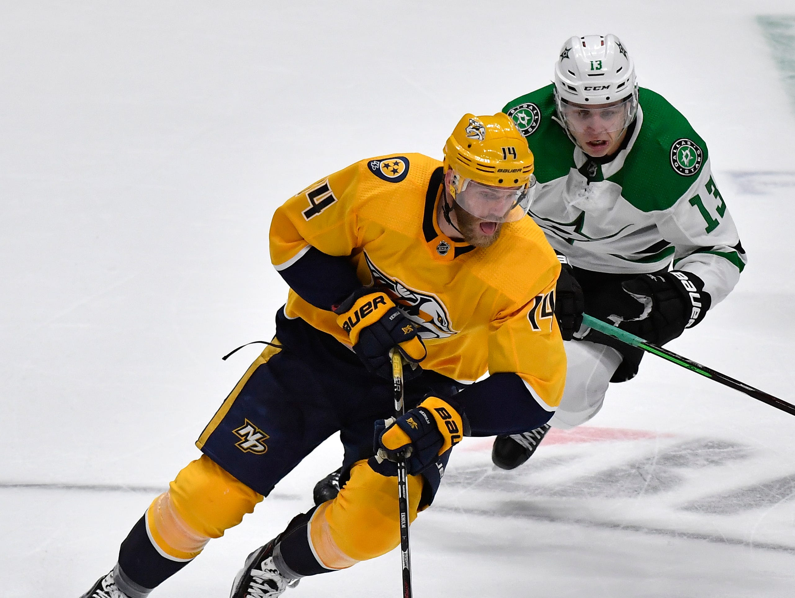 Nashville Predators defenseman Mattias Ekholm (14) moves the puck defended by Dallas Stars center Mattias Janmark (13) during the third period of the divisional semifinal game at Bridgestone Arena in Nashville, Tenn., Wednesday, April 10, 2019.