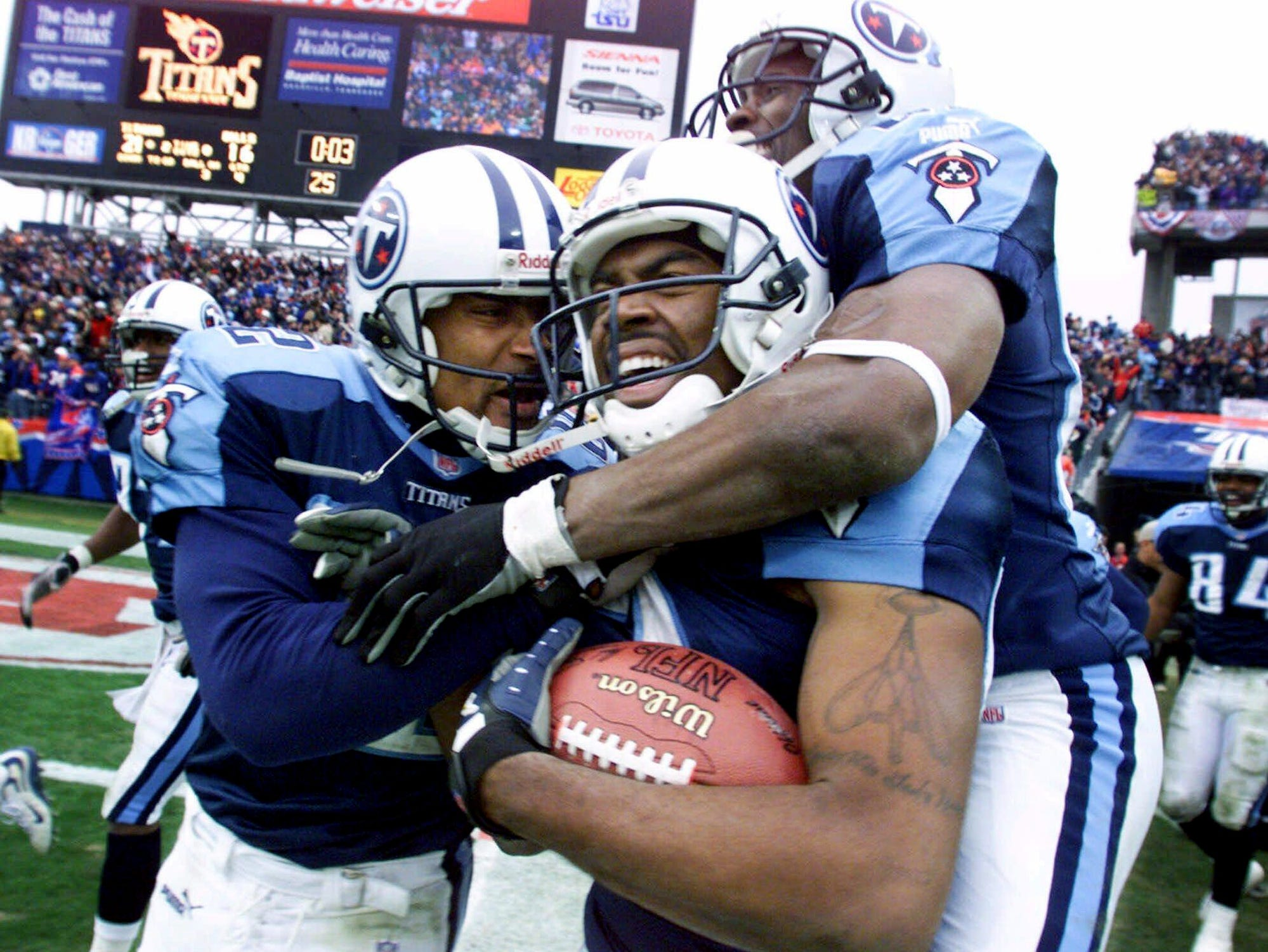 Tennessee Titans wide receiver Kevin Dyson, center, holds onto the ball as he is celebrates with teammates Yancey Thigpen, left, and Samari Rolle after returning a kickoff for a touchdown with 3 seconds left in their AFC wild card game against the Buffalo Bills for a 22-16 victory Jan. 8, 2000.