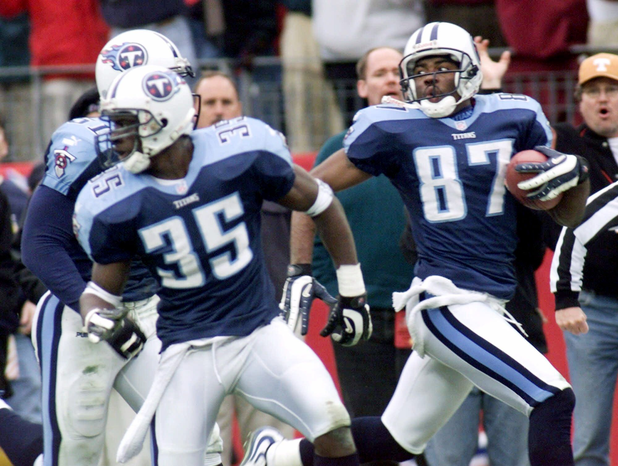 Tennessee Titans wide receiver Kevin Dyson (87) looks back as he returns a kickoff with seconds remaining in the game against the Buffalo Bills in the AFC wild card game Jan. 8, 2000. Blocking for Dyson are teammates Perry Phenix (35) and Greg Favors (51).