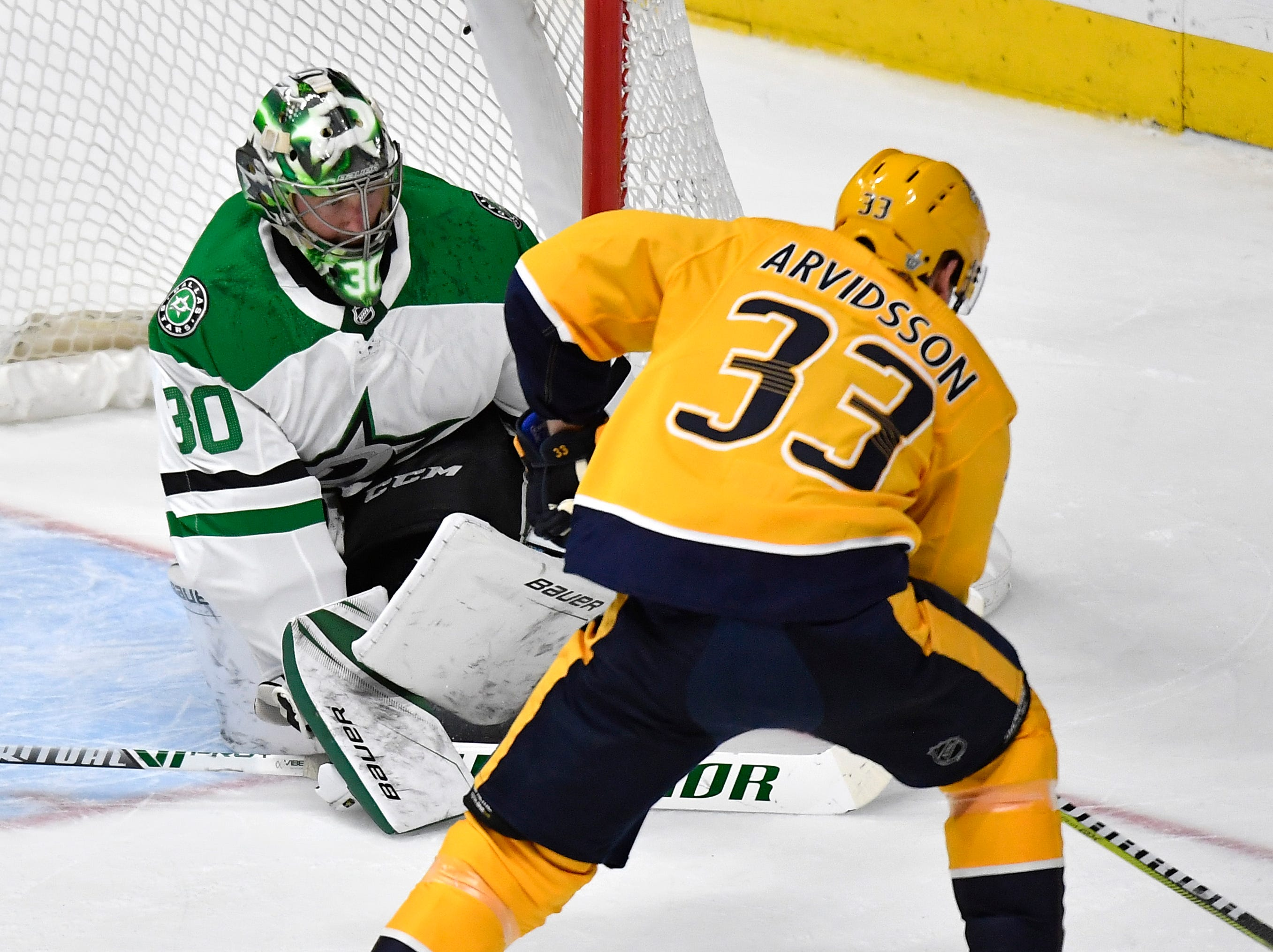 Nashville Predators right wing Viktor Arvidsson (33) moves the puck in front of Dallas Stars goaltender Ben Bishop (30) during the first period of the divisional semifinal game at Bridgestone Arena in Nashville, Tenn., Wednesday, April 10, 2019.