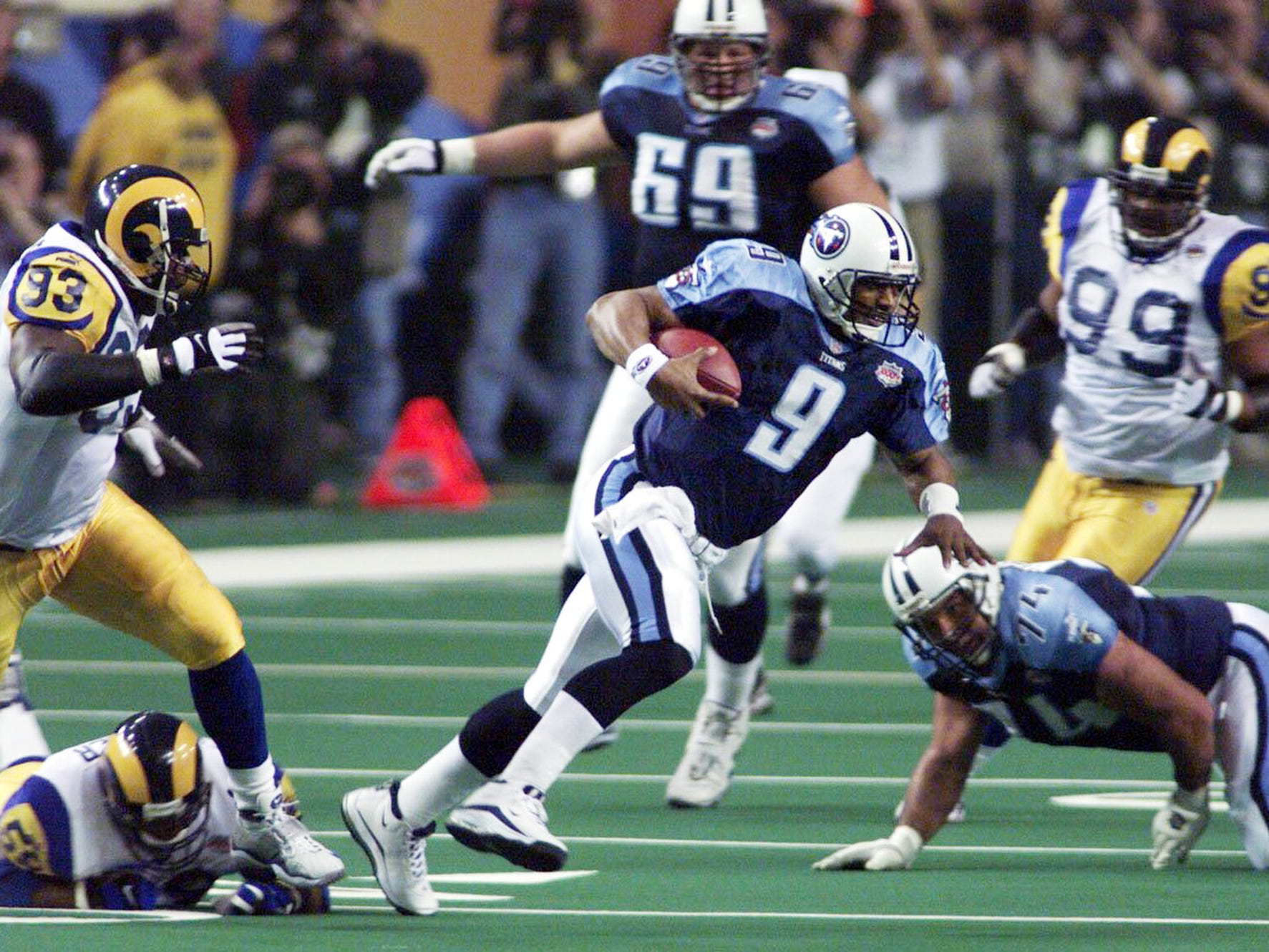 Tennessee Titans quarterback Steve McNair (9) takes off on a run to get away from St. Louis defensive end Kevin Carter (93) in the second quarter of Super Bowl XXXIV Jan. 30, 2000 in Atlanta. The Titans just fell inches short in a 23-16 Rams' victory in Super Bowl XXXIV.