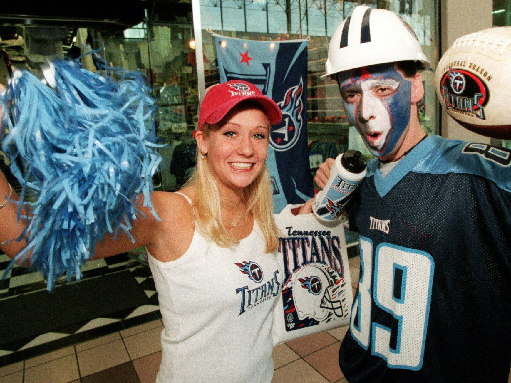 Sport Seasons employees Brandi Bagwell, left, and John Wargo wear some of the Tennessee Titans stuff like jerseys, face paint, football, pom poms, helmet, etc. to demonstrate preparation fans can make for the upcoming season Aug. 13, 1999.