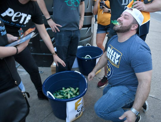 Chris Harris of Lebanon nabs a catfish squeeze toy from PETA volunteers outside Bridgestone Arena before the divisional semifinal game Wednesday, April 10, 2019.