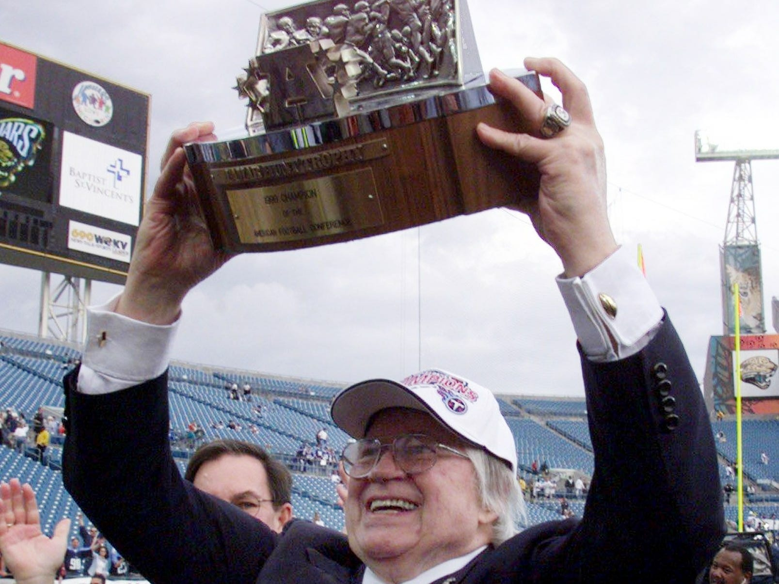 Tennessee Titans owner Bud Adams raises the AFC championship trophy to the fans at Alltel Stadium after beating the Jacksonville Jaguars 33-14 Jan. 23, 2000.