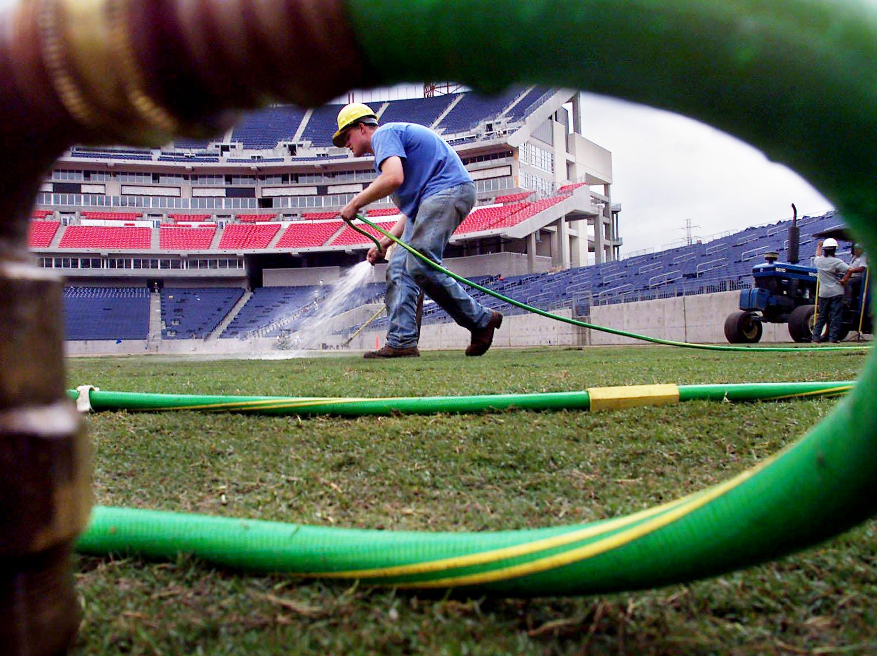 James Newberry, a student at Iowa State, waters the just-laid turf at the new Titans stadium in East Nashville May 18, 1999. After the special turf is laid, Newberry will stay in Nashville for a month to keep it in good shape.