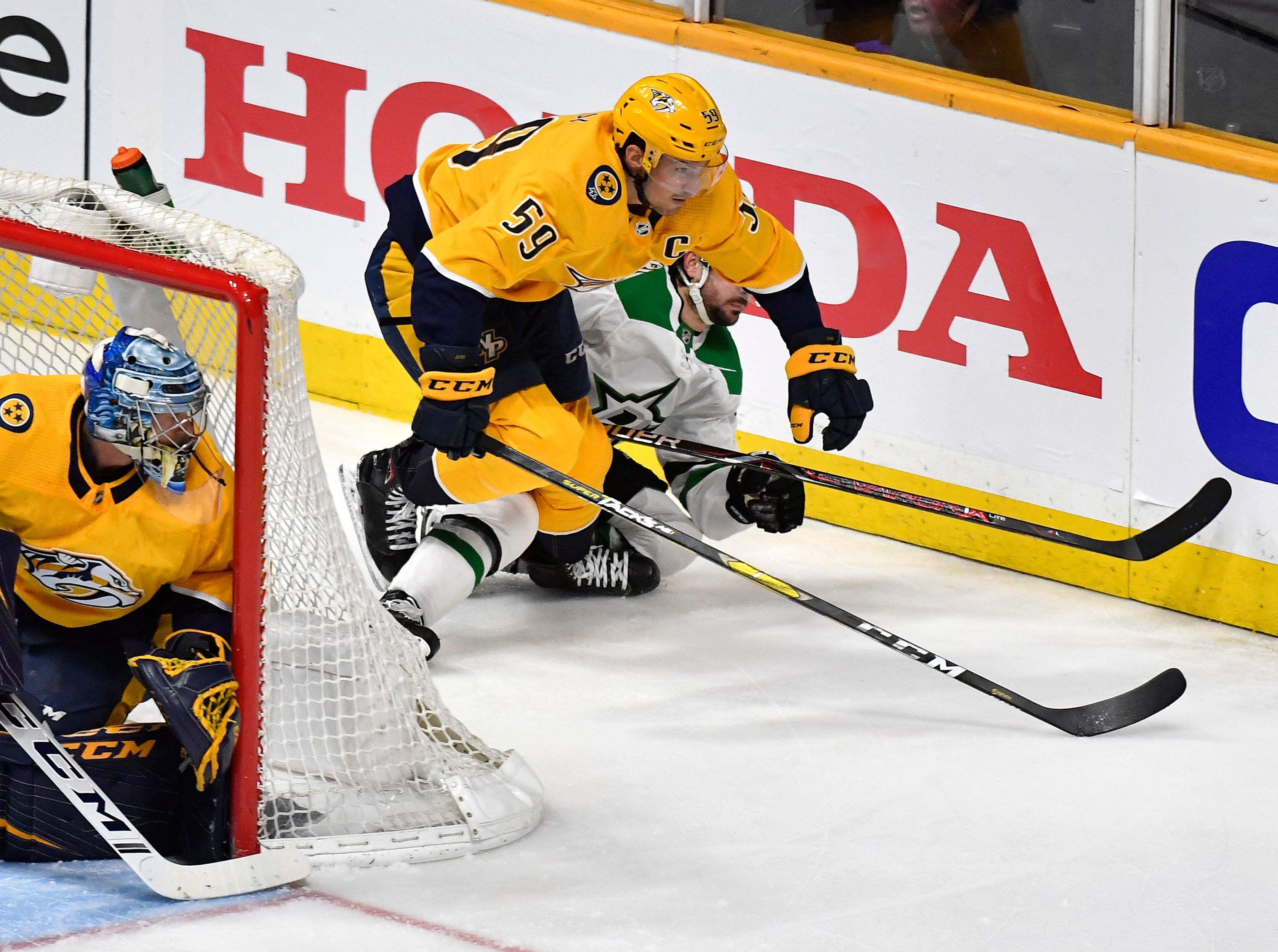 Nashville Predators defenseman Roman Josi (59) and Dallas Stars center Mats Zuccarello (36) battle for the puck behind Nashville Predators goaltender Pekka Rinne (35) during the second period of the divisional semifinal game at Bridgestone Arena in Nashville, Tenn., Wednesday, April 10, 2019.