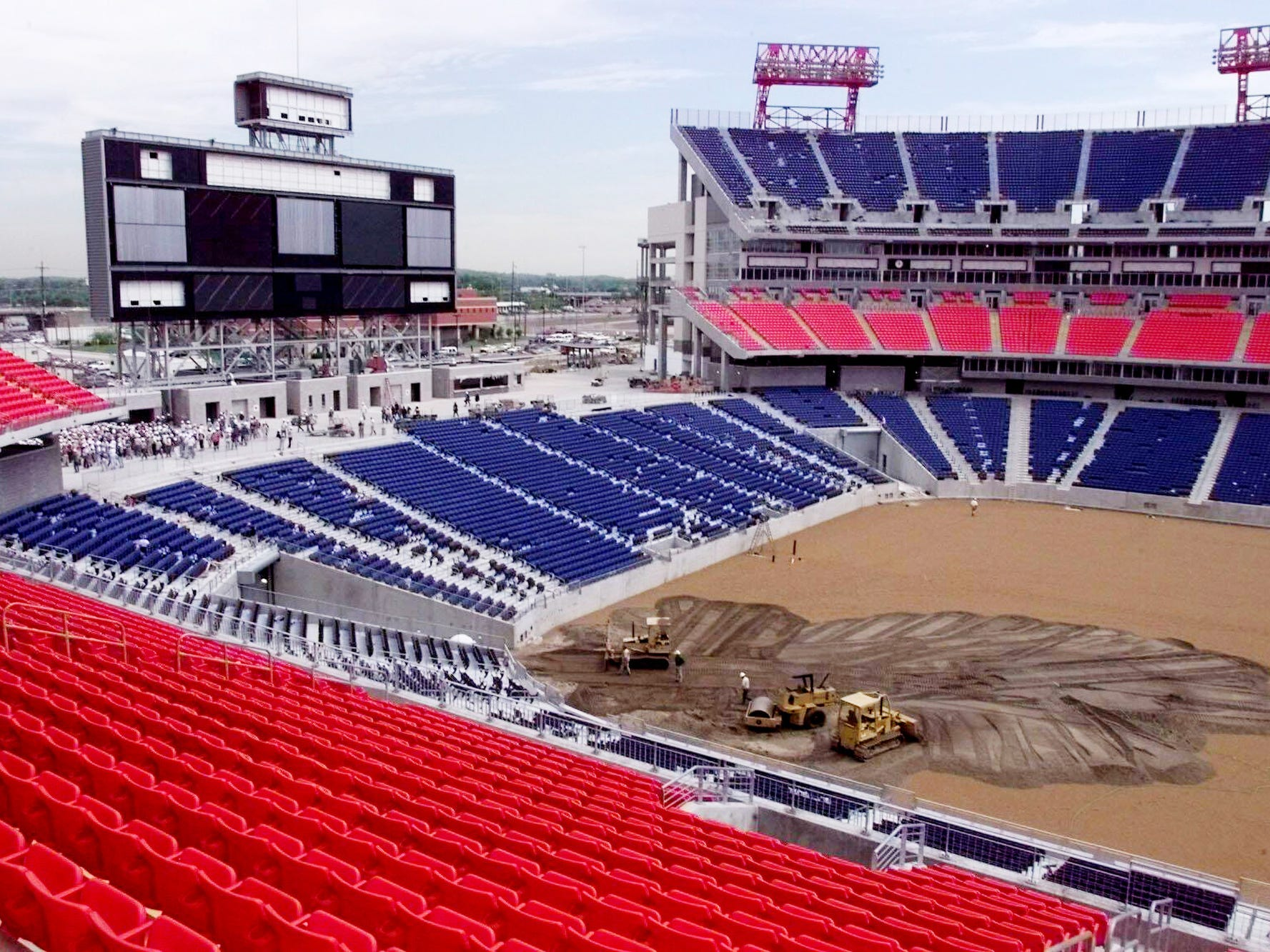 Dirt is being spread on the playing field at the football stadium as the team watches from the north stands May 3, 1999.