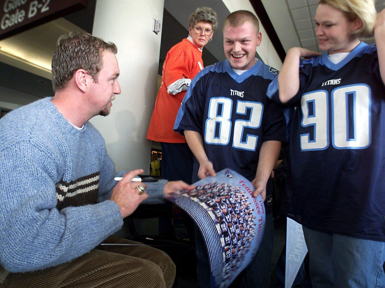 Craig Hentrich punter of the Tennessee Titans signs his autograph for Thomas Smith and Heather Smith of Nashville at the Nashville International Airport gate Jan. 15, 2000 before leaving for Indianapolis to face the Colts in the divisional play-off game.