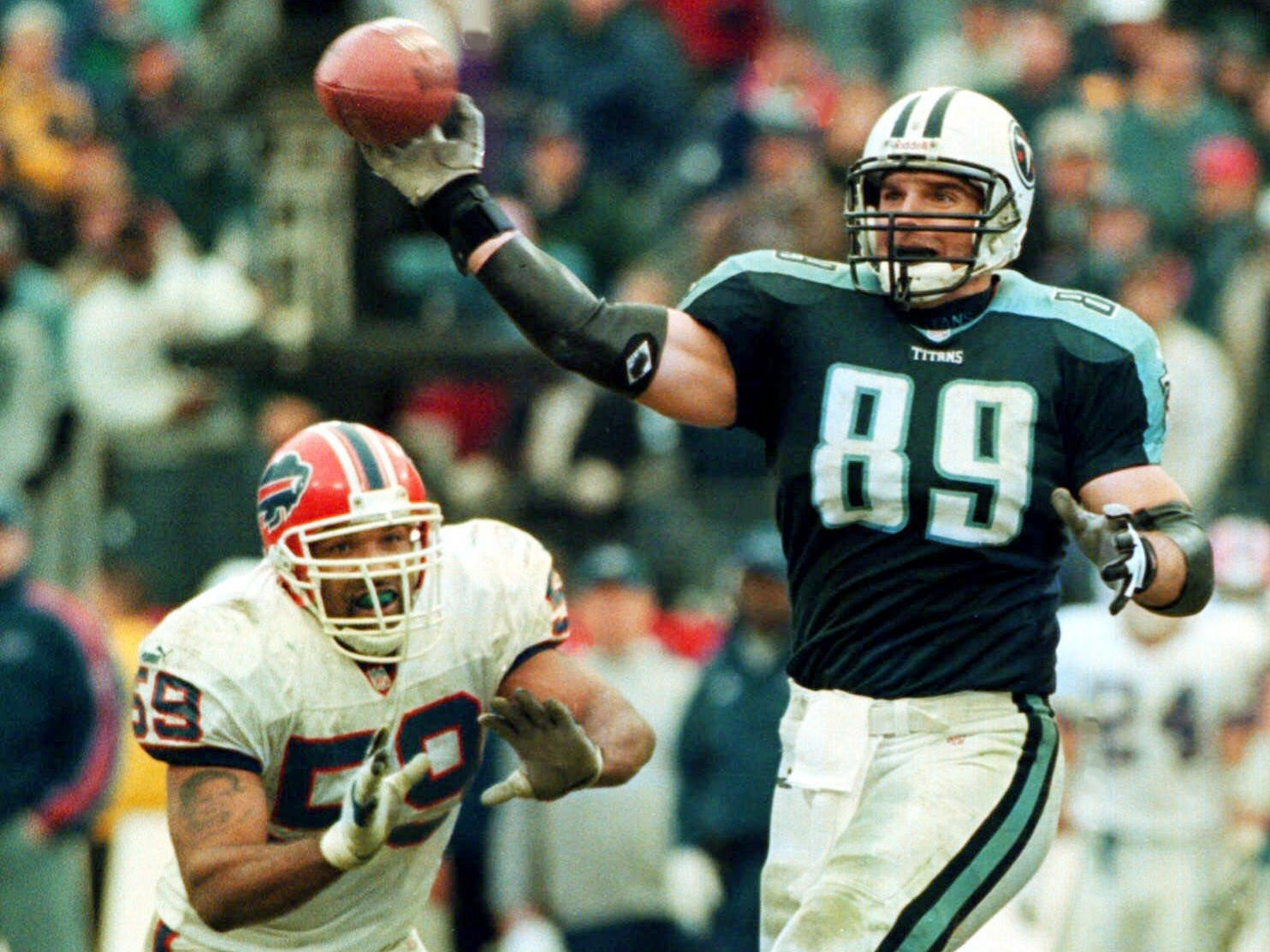 With Buffalo Bills defender Sam Rogers (59) moving in, Tennessee Titans' Frank Wycheck laterals the ball across the field to teammate Kevin Dyson at Adelphia Coliseum Jan. 8, 2000.