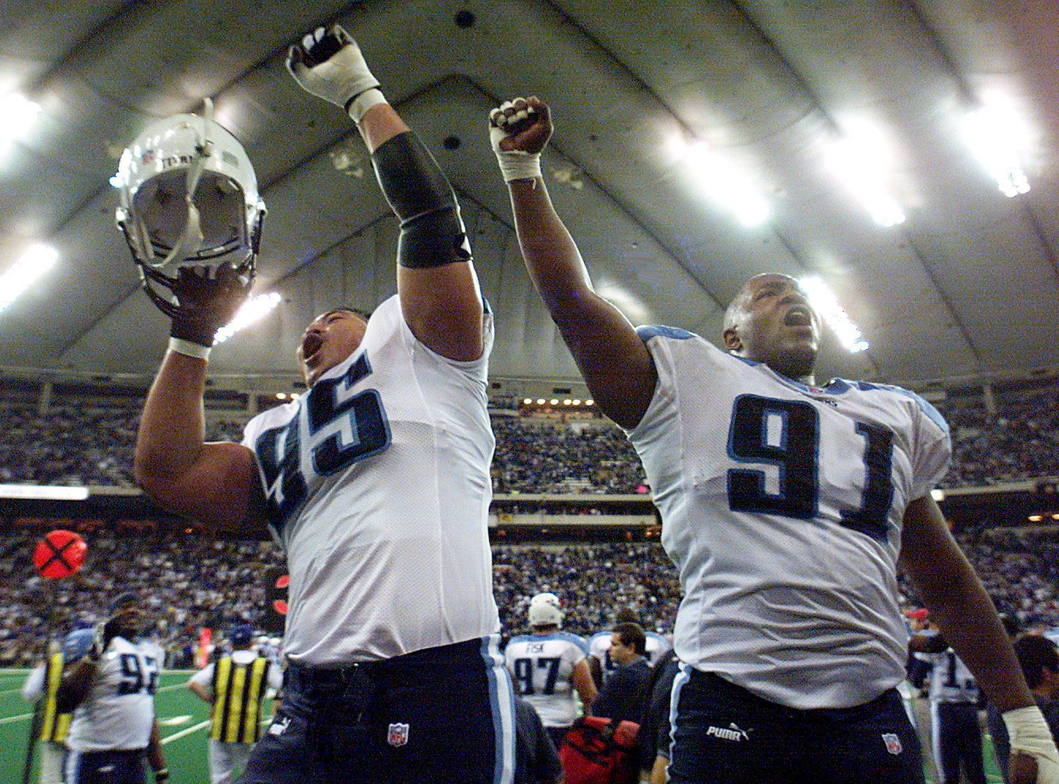 Joe Salave'a (95) and Josh Evans (91) of the Tennessee Titans celebrate on the sideline after defeating the Indianapolis Colts 19-16 at the RCA Dome in the AFC divisional playoff game at Indianapolis Jan. 16, 2000.