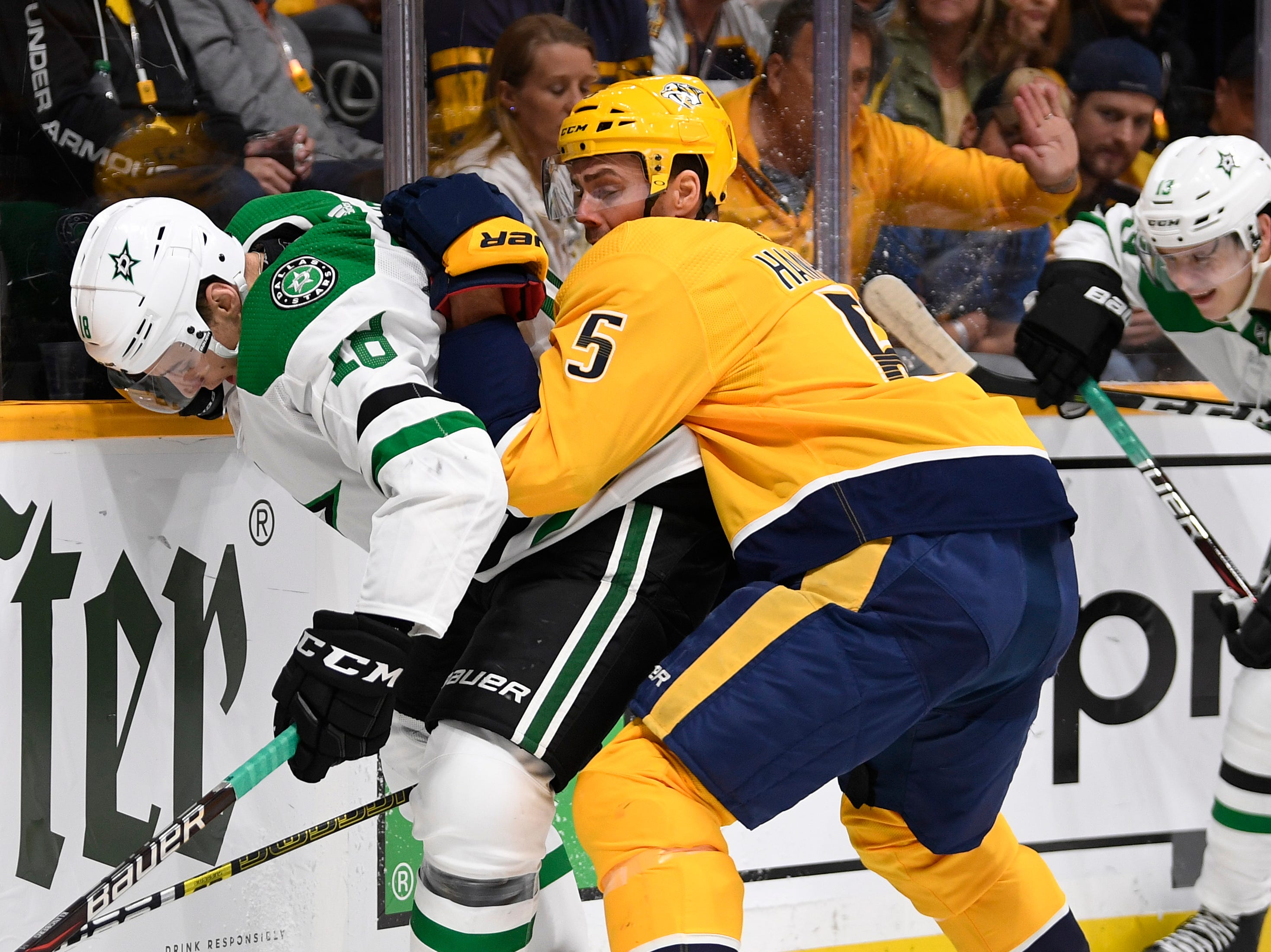 Nashville Predators defenseman Dan Hamhuis (5) and Dallas Stars center Tyler Pitlick (18) battle for the puck along the boards during the second period of the divisional semifinal game at Bridgestone Arena in Nashville, Tenn., Wednesday, April 10, 2019.