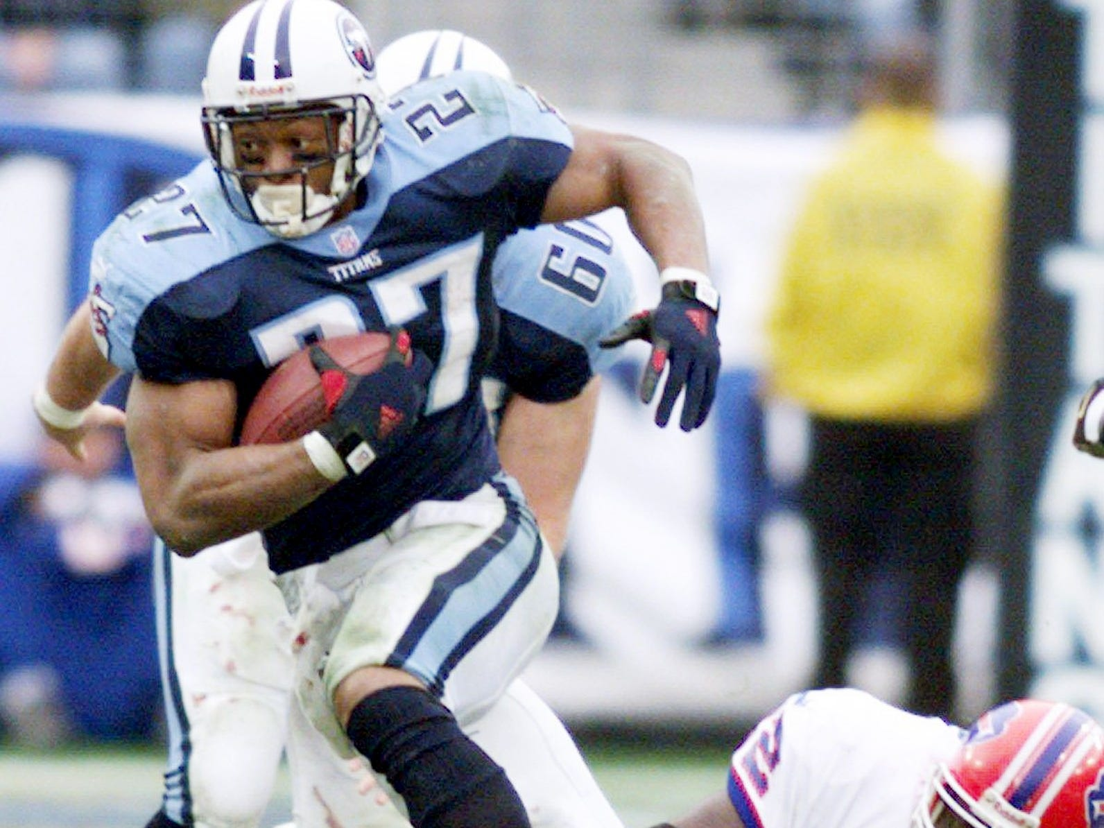 "Tennessee Titans running back Eddie George (27) runs past the defense of Buffalo Bills during the 3rd quarter Jan. 8, 2000. The Titans defended the Bills 22-16 on the last seconds ""Music City Miracle"" in the AFC Wild Card game at home."