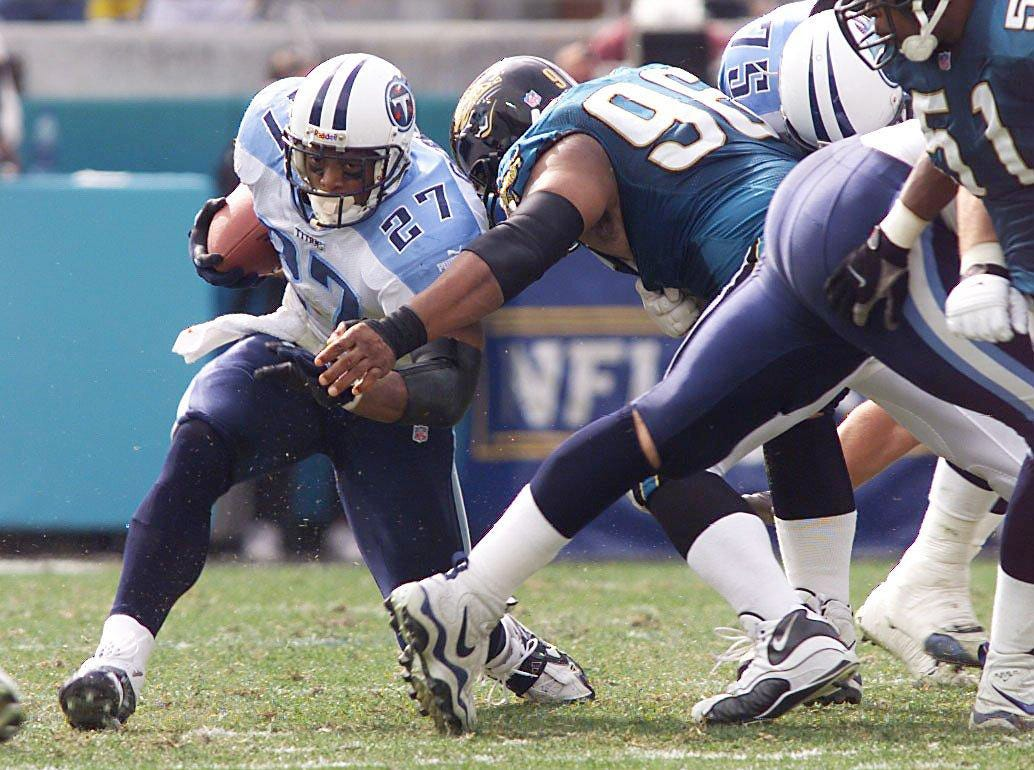 Tennessee Titans running back Eddie George (27) rushes for yardage during second quarter action against defender Gary Walker of the Jacksonville Jaguars at Alltel Stadium in Jacksonville Jan. 23, 2000. The Titans won the AFC championship game 33-14.