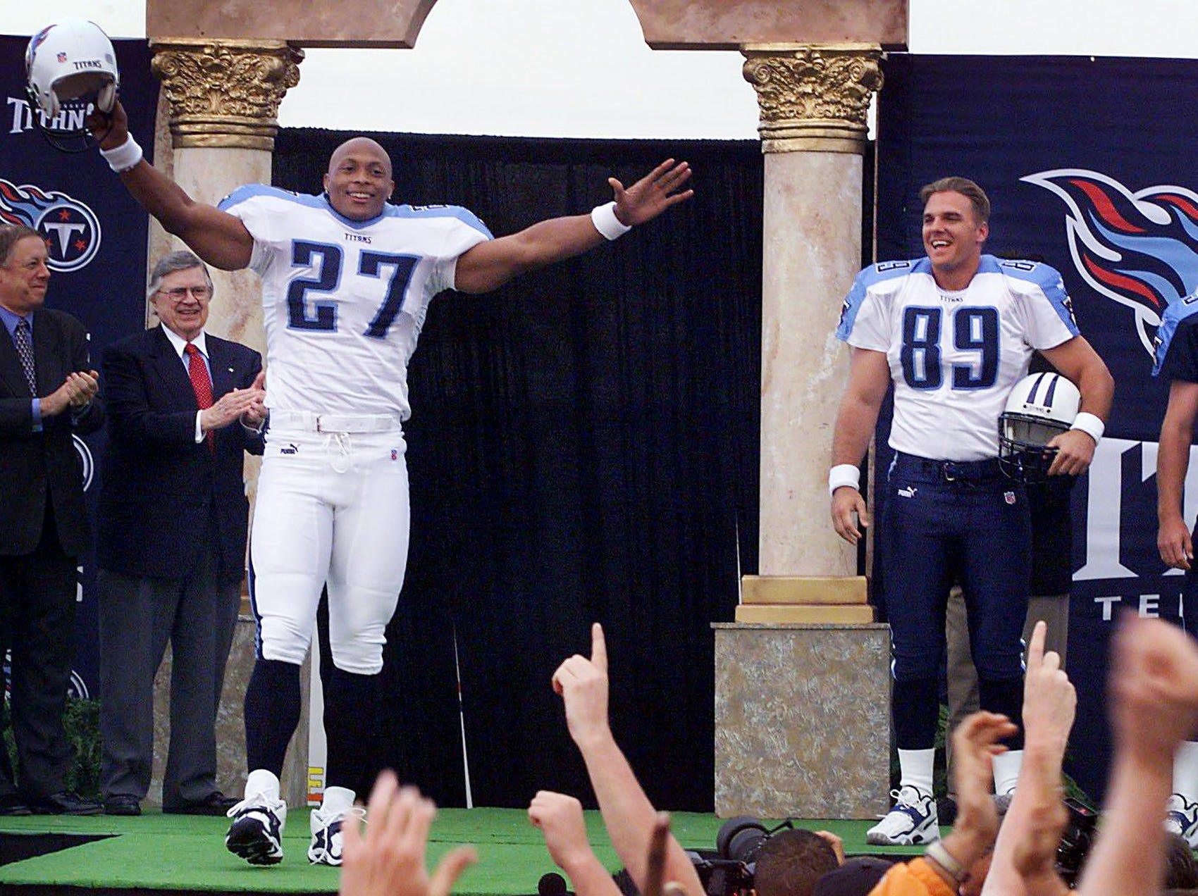 Star running back Eddie George (27) of the Tennessee Titans shows off the new uniform with teammates Frank Wycheck (89) and Craig Hentrich (15) for the fans at the unveiling of the team uniforms April 13, 1999. Looking on is Gov. Phil Bredesen, left, and Titans owner Bud Adams.
