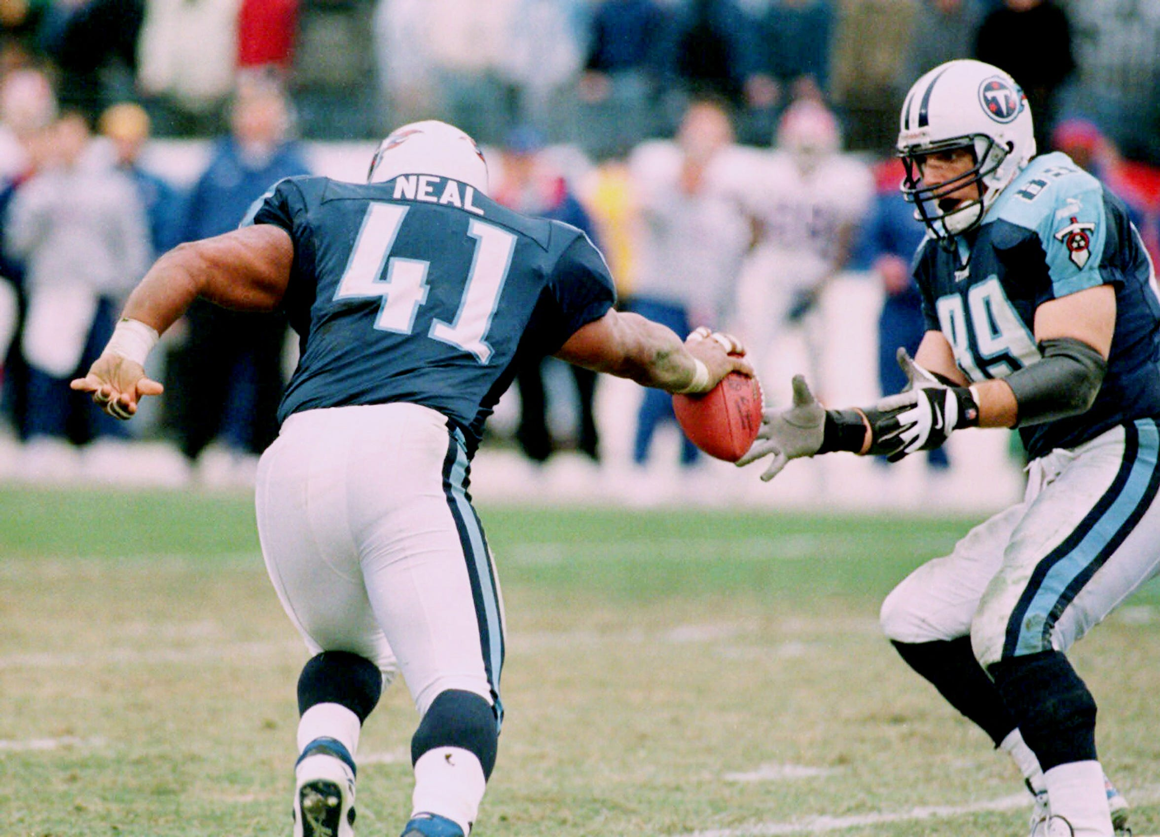 Tennessee Titans fullback Lorenzo Neal (41) hands the ball off to tight end Frank Wycheck (89) after Neal received a kickoff from the Buffalo Bills with 16 seconds left of the game and the Bills leading 16-15 in the AFC wild card game at Adelphia Coliseum Jan. 8, 2000.