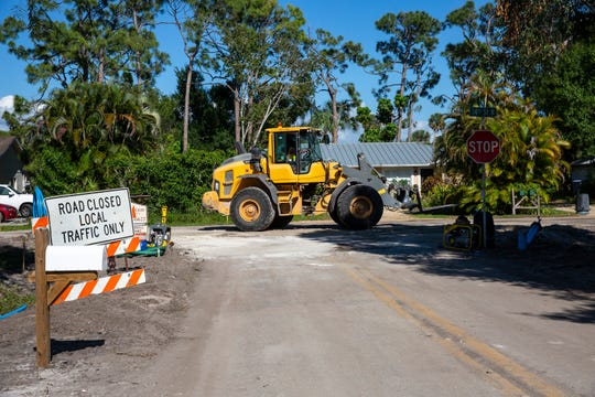 A bulldozer involved in sewer system work moves across Cooper Drive and 14th Street North on Thursday, April 11, 2019 in Naples.