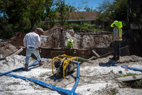 Crews work to connect Ridge Street residents to city sewer, Thursday, April 11, 2019 in Naples.