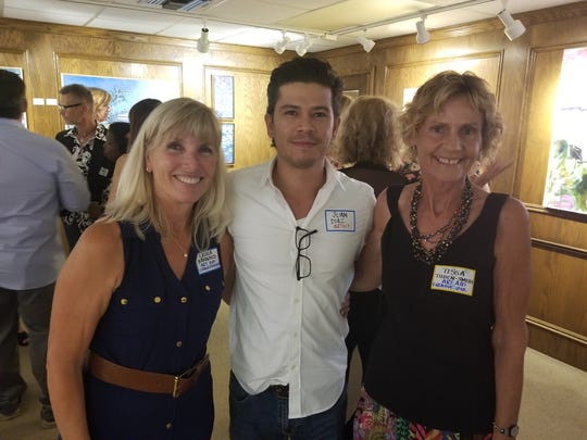 Laura Barnard, left, with artist Juan Diaz and volunteer Tessa Tilden-Smith at the Art Aid launch party