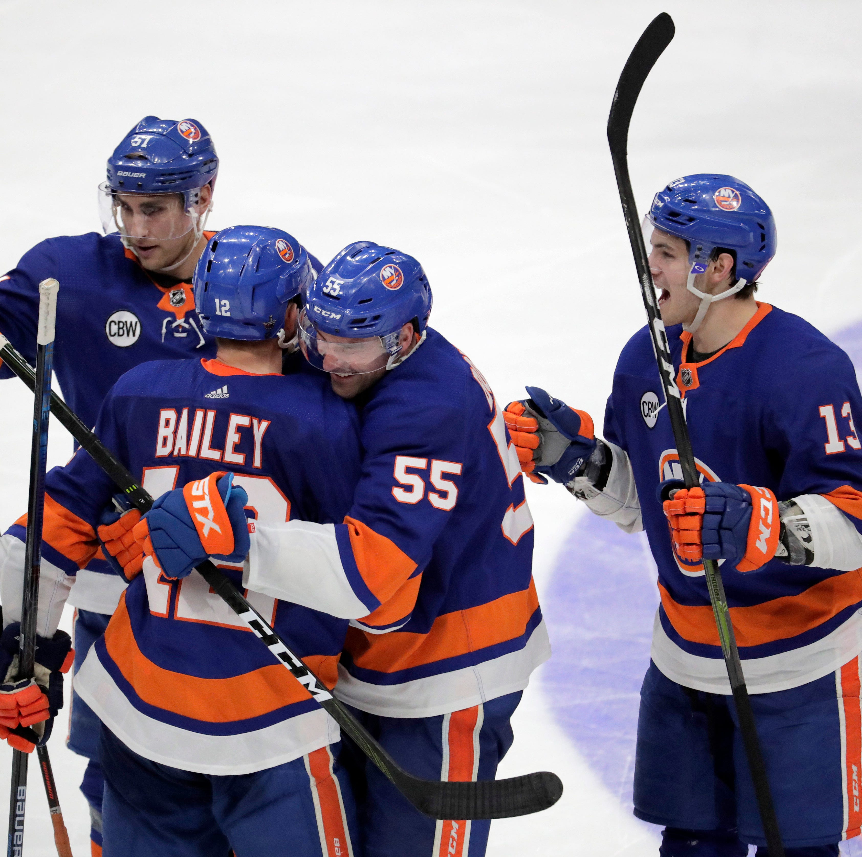 New York Islanders right wing Josh Bailey is hugged by defenseman Johnny Boychuk (55) as teammates celebrate after Bailey scored in overtime against the Pittsburgh Penguins during Game 1 of an NHL hockey first-round playoff series, Wednesday, April 10, 2019, in Uniondale, N.Y. The Islanders won 4-3. (AP Photo/Julio Cortez)