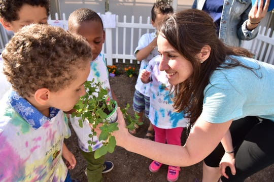 Kathleen Moran of the Binder Autism Center offers the smell of a chocolate mint plant to Alex Camilo at the garden of St. Joseph's Wayne Hospital on Tuesday. Binder Autism Center clinicians are using gardening as the vehicle to teach and practice social skills to children affected with autism.