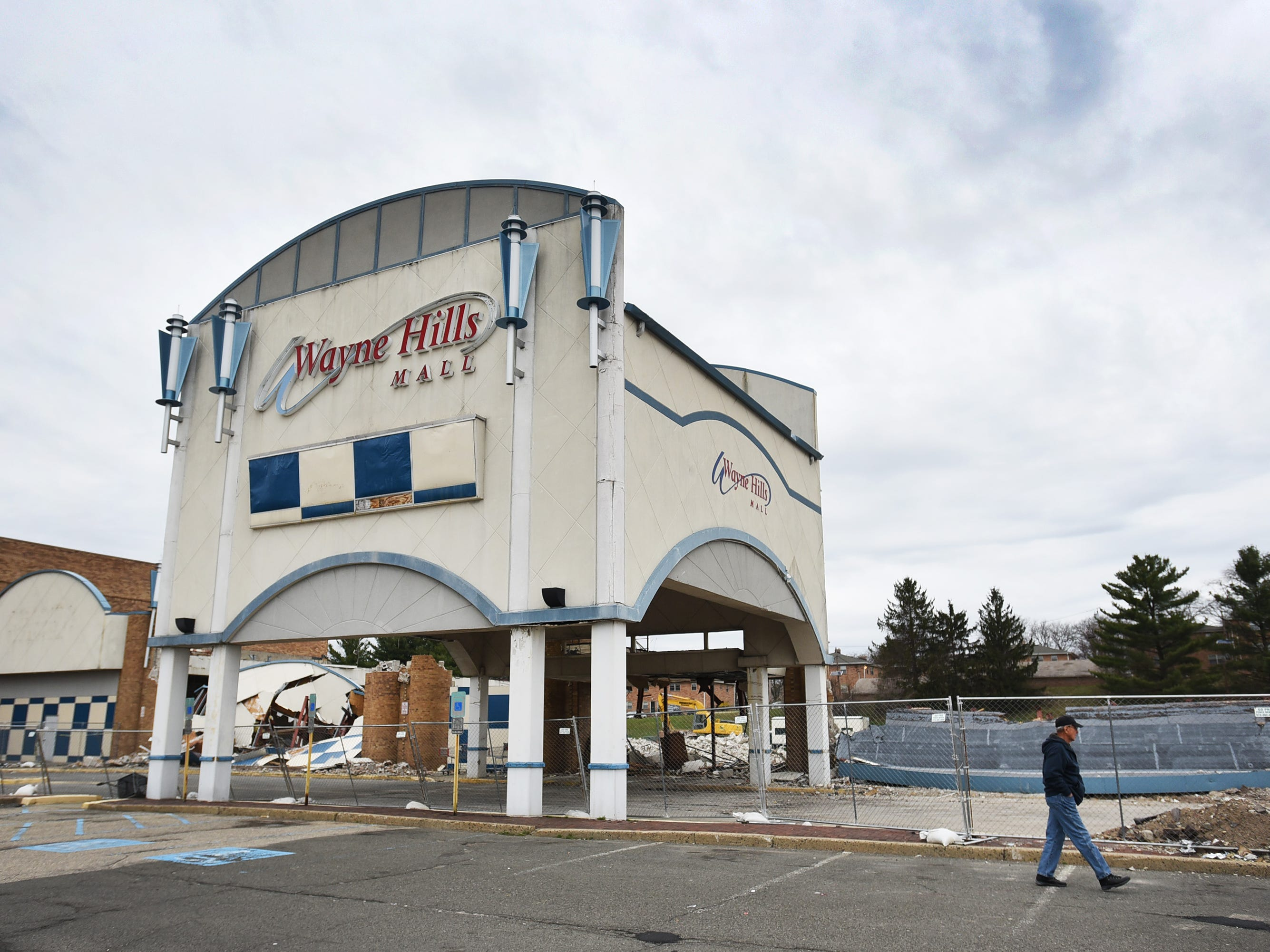 A shopper passes by as the final demolition of the Wayne Hills Mall take place, photographed in Wayne on April 11, 2019.