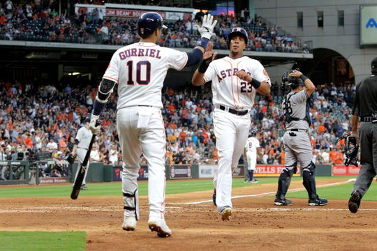 Houston Astros left fielder Michael Brantley (23) celebrates with third baseman Yuli Gurriel (10) after scoring a run against the New York Yankees during the third inning at Minute Maid Park.