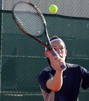 Sophomore Wildcat Carter Williams makes his overhead shot from the baseline during Tuesday's District 3-5A tennis action.