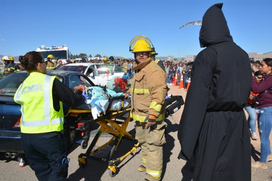 First responders attend to student volunteer victims while the grim reaper hovers over a crash site at a Shattered Lives program on Thursday, April 11, 2019, at Chaparral High School. Most of the student body lined the front of the school to see the simulated DWI crash demonstration.