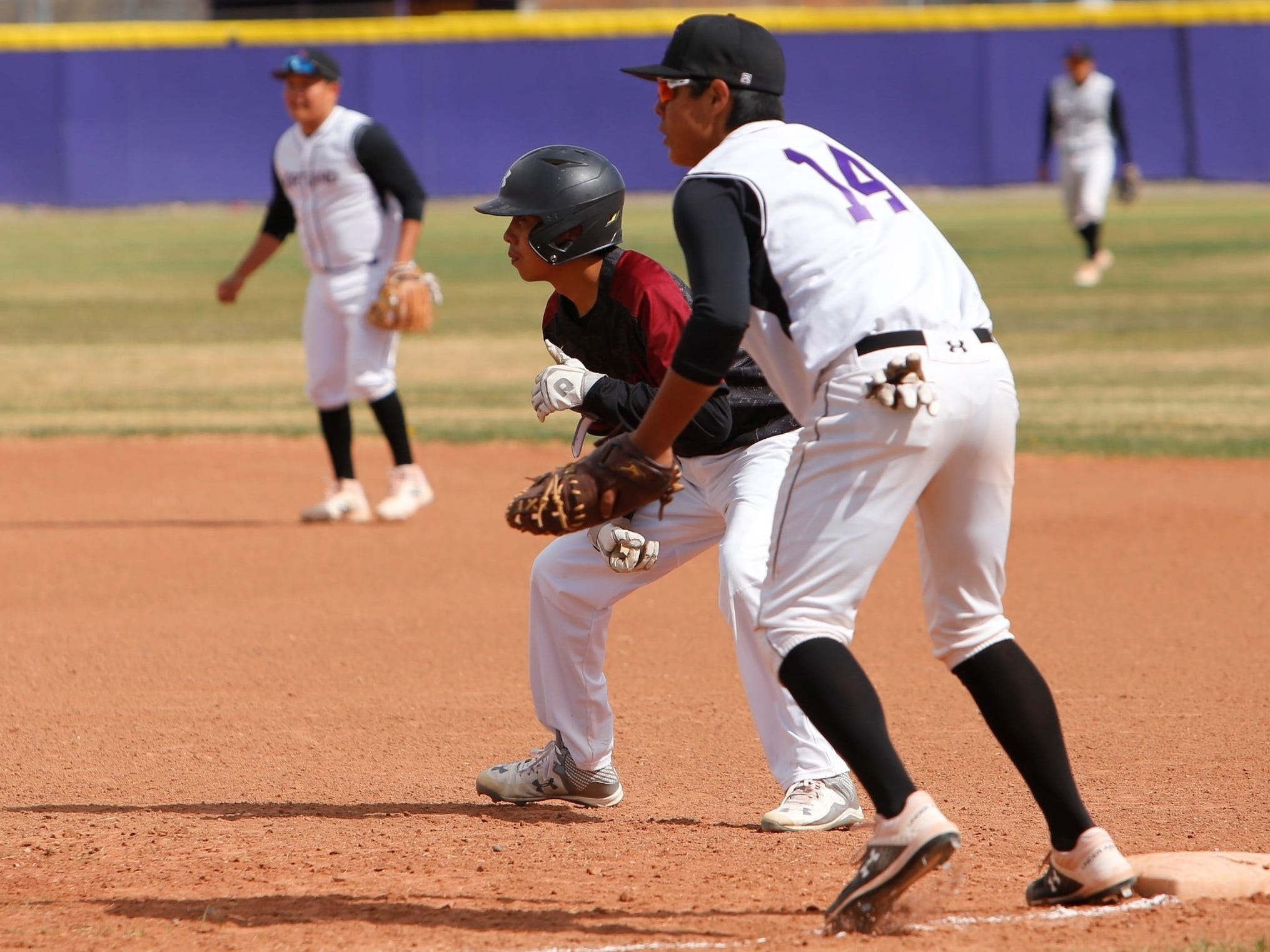 Shiprock's Raekwon Smart looks to take off toward second base against Kirtland Central's Justin Williams (14) during Thursday's District 1-4A game at KCHS.