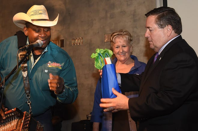 Louisiana Lt. Gov. Billy Nungesser accepts a St. Landry Parish gift from Geno Delafose while Port of Krotz Springs Director Lynn LeJeune looks on Tuesday at the 36th annual Port Association of Louisiana Conference Reception at Evangeline Downs.