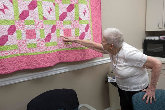 Lois Watson, a longtime volunteer at Baptist Medical Park, shows off a quilt she made with a patient on April 10.