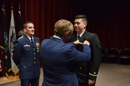 PensacolanativeEnsign Alexander K. Dinellireceived his wings of gold from his father, retired Navy Capt. Lance Dinelli, in a ceremony March 22 at Whiting Field.