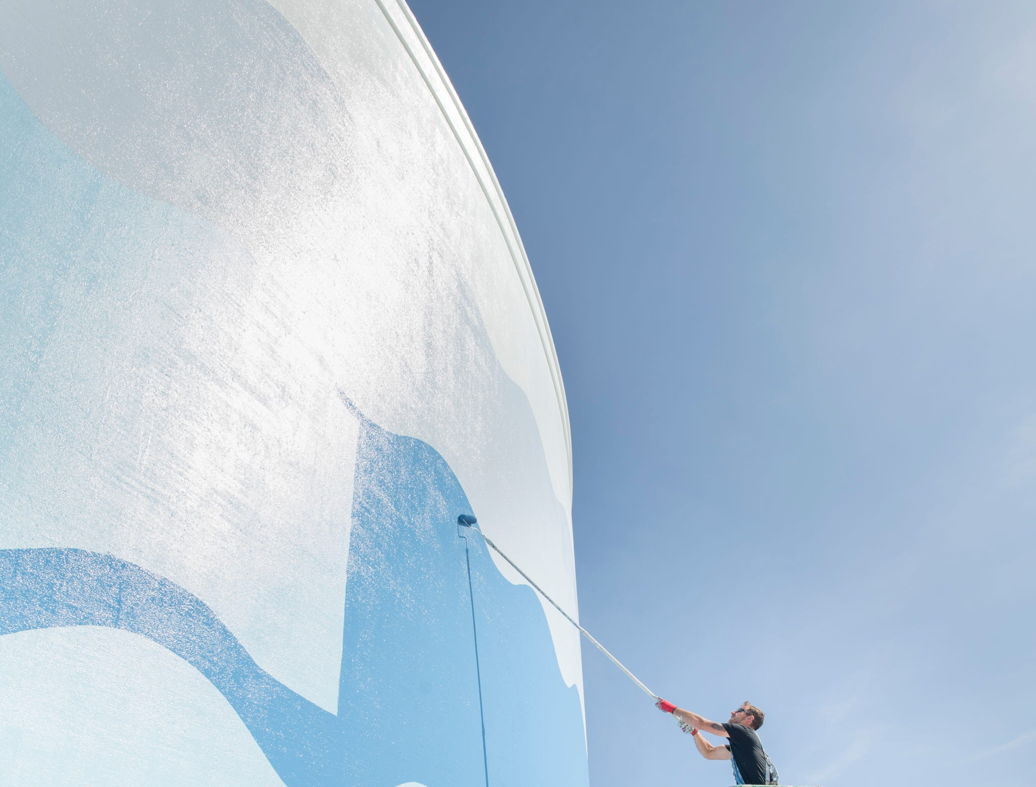 Robert Lawson, of Jetco Ltd., bottom, looks up as coworker Michael Wiegel paints the newest water tower along Pensacola Beach Blvd. in Pensacola Beach on Thursday, April 11, 2019.