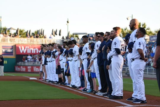 The Pensacola Blue Wahoos stand for the national anthem prior to the team's home opener on April 10, 2019.