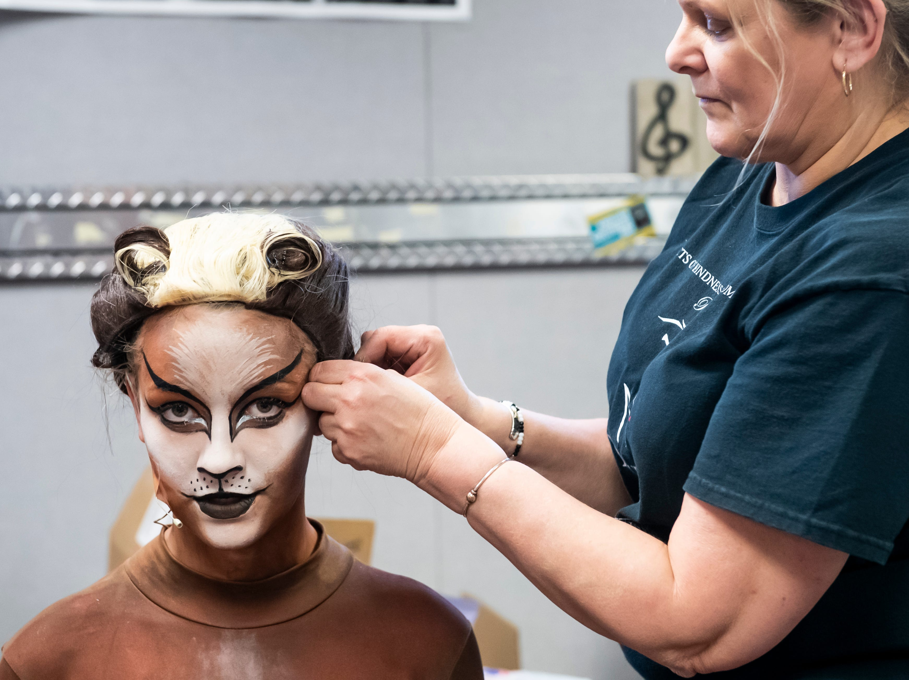"""Susan Taylor adjusts Finley Miller's wig at a dress rehearsal for Hanover High School's production of """"Cats"""" on Wednesday, April 10, 2019."""